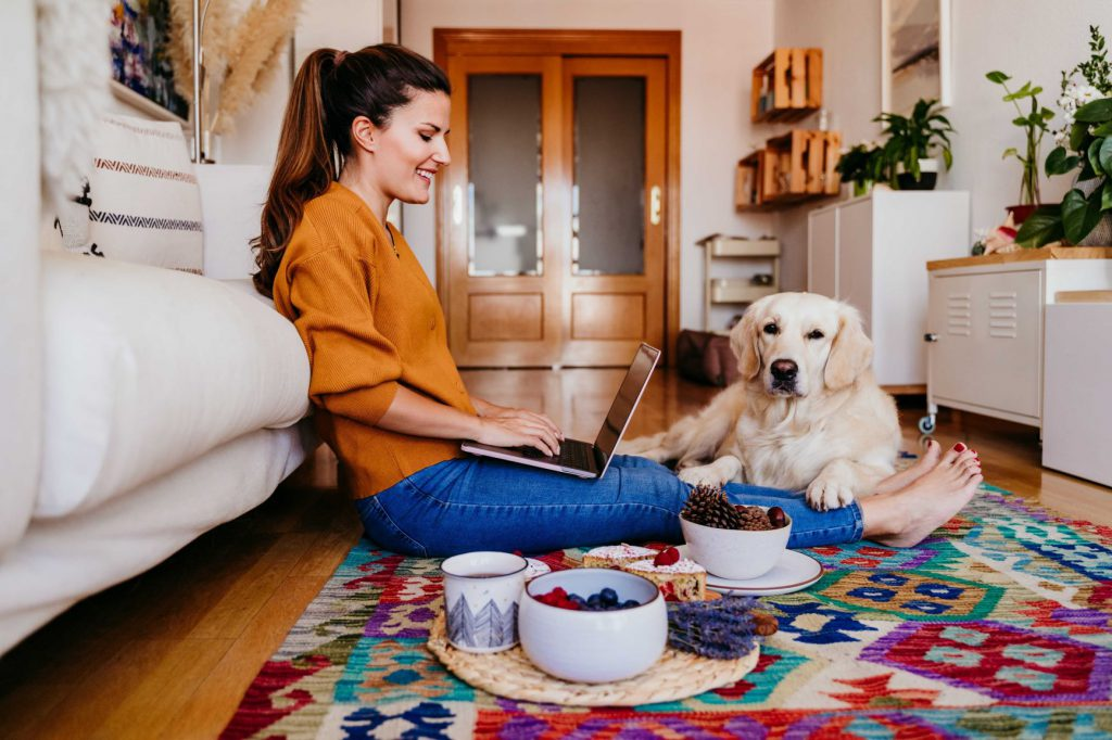 kobieta pracuje zdalnie z domu z psem rasy golden retriever