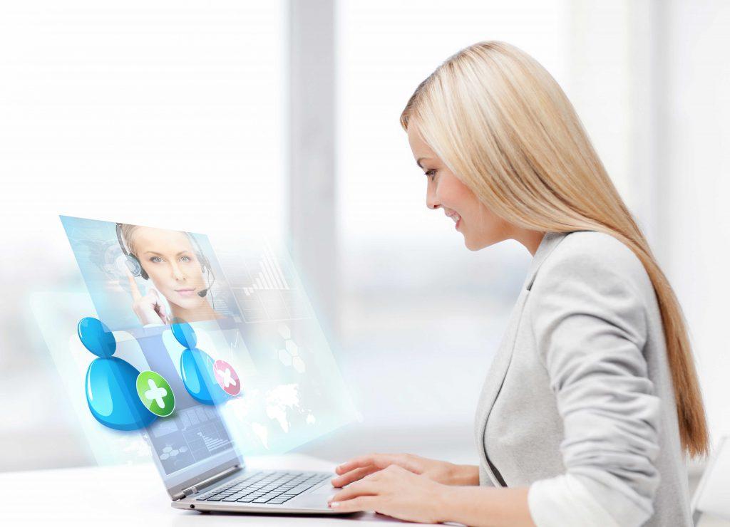 wirtualna Asystentka pracuje na laptopie siedząc przy biurku.